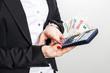 Frauenhand mit Geld und Taschenrechner
