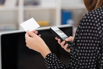 frau hält visitenkarte und telefon in den händen