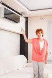 Woman holding a remote control air conditioner