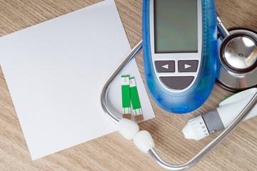 Blutzuckermessgerät mit Stethoskop und leerem Zettel