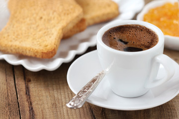 Breakfast concept - cup of black coffee with toasts and jam