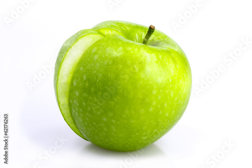 Green apple with a slice taken out on a white background