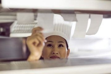 Female chef going through cooking checklist at kitchen