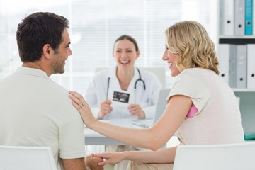 Expectant couple with doctor in clinic