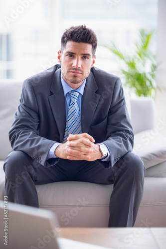 Smiling businessman sitting on the sofa looking at camera