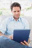 Focused man sitting on the couch using his tablet