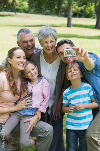 Man taking picture of extended family at park
