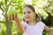 Close-up of girl holding apple in park