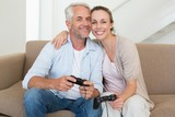 Happy couple having fun on the couch playing video games