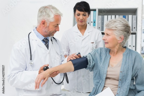 Doctor measuring blood pressure of a senior patient