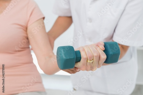 Mid section of physiotherapist assisting woman to lift dumbbell