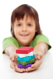 Colorful modelling clay blocks in boy hands