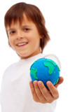 Smiling boy holding modelling clay earth
