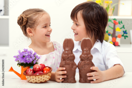 Happy kids at easter time with large chocolate bunnies
