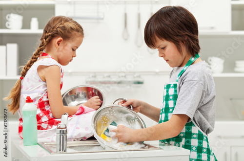 Grumpy kids doing home chores - washing dishes