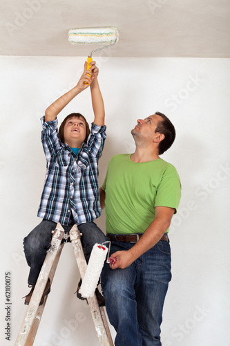 Boy helping his father to paint the room