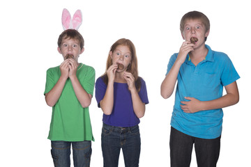 three young children eating easter eggs