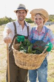 Smiling couple with fresh vegetables in field
