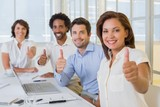 Business people gesturing thumbs up in meeting at office