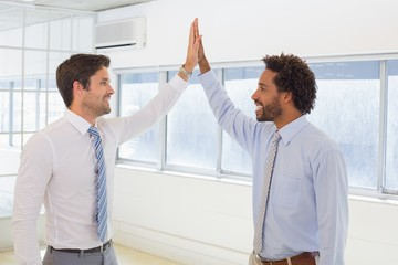 Smiling businessmen joining hands together in office
