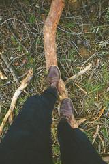 Overhead of man boots treading a pine log.