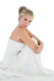 Sensuous bride hugging knees over white background