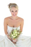 Bride holding flower bouquet against white background