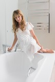 Beautiful woman sitting on the edge of bath tub in the bathroom