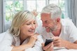 Cheerful mature couple reading text message at home