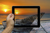 Taking picture with digital tablet of a sunset in Zanzibar