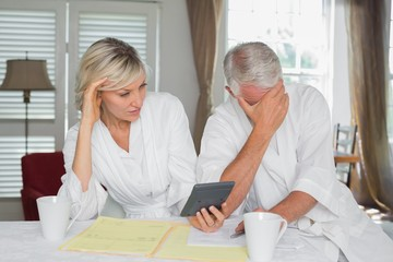 Worried mature couple with home bills and calculator