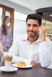 Smiling man using mobile phone in coffee shop