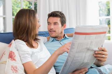 Relaxed happy couple reading newspaper on couch