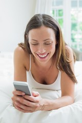 Smiling woman text messaging in bed