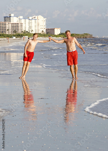 father and son enjoy sunset at the beach