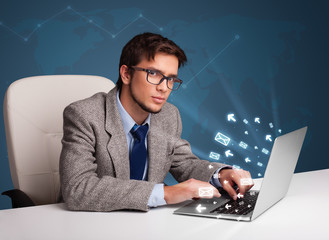 Young man sitting at dest and typing on laptop with message icon