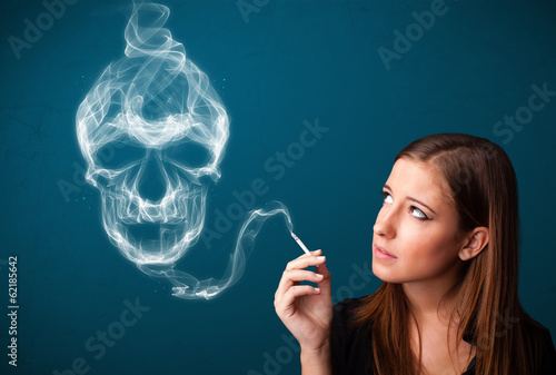 Young woman smoking dangerous cigarette with toxic skull smoke - 62185642