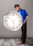 Attractive boy holding a huge clock