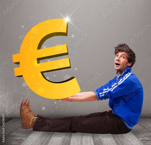 Good-looking boy holding a big 3d gold euro sign