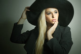 Beautiful Blond Woman in Black Hat.Topcoat.Spring Collection