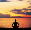 Sunset meditation. Silhouette of a woman doing yoga exercise.