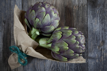 two artichokes on woody table