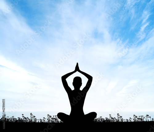 Silhouette of a young meditating woman on the sky