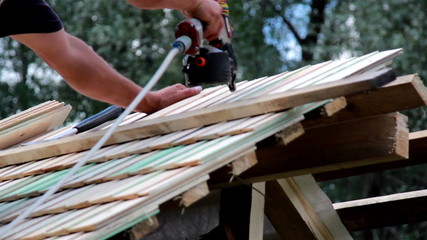 Using a machine to nail in the cedar wooden shingle roof tiles
