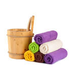 Wooden bucket with ladle for the sauna and stack of clean towels