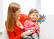 happy mother and daughter with pinwheel toy