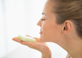 Young woman smelling soap bar