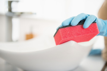 Closeup on housewife cleaning sink with sponge