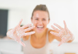 Closeup on smiling young woman showing hands with soap foam