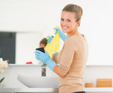 Happy housewife with spray bottle and sponge in bathroom